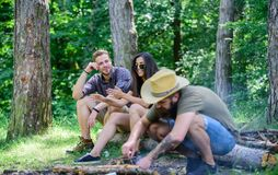 Le hippie barbu brutal campant d'homme de forêt d'amis de société prépare le feu du guide final de forêt des feux photos stock