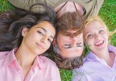 Le hippie barbu d'homme s'étendent sur l'herbe avec la blonde et la brune de deux filles Blonde et brune étendues sur ses épaules images stock