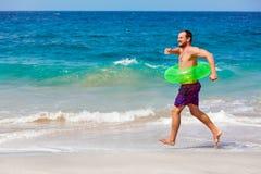 Le hippie barbu en anneau gonflable ont l'amusement des vacances de plage Photographie stock libre de droits