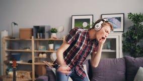 Le hippie beau a l'amusement en appartement écoutant la musique avec des écouteurs dansant et chantant appréciant le temps libre  banque de vidéos