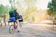 Le hippie un homme avec la bicyclette en nature détendent le temps en vacances Photographie stock