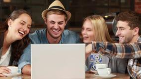 Le hipstervänner som skrattar över en bärbar dator lager videofilmer