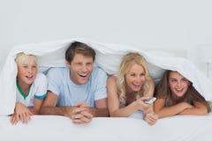 Le hållande ögonen på TV för familj Arkivfoton