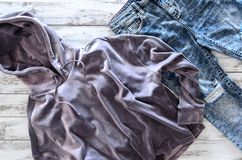 Le hoodie violet de velours de l'habillement des femmes, acide a lavé des jeans courtisent dessus photographie stock