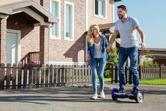 Le hoverboard comblé d'équitation d'homme avec ses wifes aident Photos stock