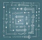 Le icone disegnate a mano della freccia hanno messo sul bordo di gesso blu Fotografia Stock