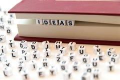 Le idee di parola scritte con le lettere fra un libro impagina il fondo bianco con le lettere sparse intorno al concetto della le immagini stock libere da diritti