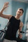 Le idrottsmannen med sportar buteljera och hänga löst den vinkande handen i idrottshall Royaltyfri Bild
