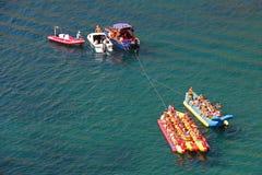 Le imbarcazioni a motore stanno preparando rotolare la gente su una barca di banana Fotografia Stock