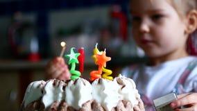 Le inserzioni e le luci della ragazza le candele in lei dolce per quattro anni stock footage