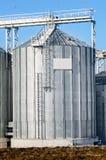 Le installazioni complesse del silo per lo stoccaggio di grano che sta nel arato Immagini Stock