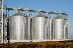 Le installazioni complesse del silo per lo stoccaggio di grano che sta nel arato Immagine Stock Libera da Diritti