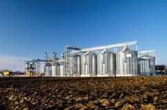 Le installazioni complesse del silo per lo stoccaggio di grano che sta nel arato Immagine Stock