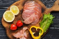 Le jambon coupé sur une planche à découper, tomates-cerises, laitue part, citron, poivre jaune, vieux fond noir rustique Image stock