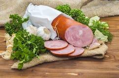 Le jambon a coupé en tranches la saucisse de proc avec l'ail et l'herbe Images stock