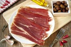 Le jambon espagnol de serrano et les olives noires ont servi de tapas Photographie stock