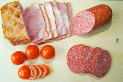 Le jambon, le salami, et les tomates sont sur le conseil image libre de droits