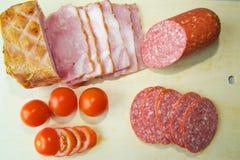 Le jambon, le salami, et les tomates sont sur le conseil photo stock