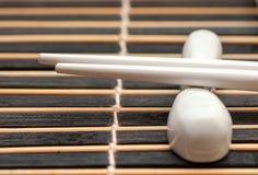 Le Japonais colle le hashi sur le couvre-tapis foncé Image libre de droits
