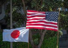 Le Japonais et les drapeaux des Etats-Unis entrant dans le vent se sont tenus par des flagbearers Image libre de droits