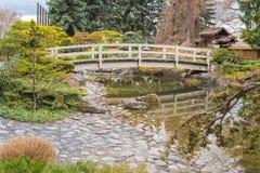 Le jardin japonais avec le pont et le koi s'accumulent dans le printemps Image stock