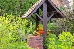 Jardin de fleur avec le puits de pierre image libre de for Jardin pittoresque