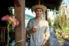 Le jardinier de type dans un chapeau de paille se tient avec le verre en plastique dans sa main à côté d'une véranda en bois dans image stock