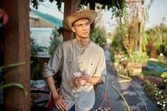 Le jardinier de type dans un chapeau de paille se tient avec le verre en plastique dans sa main à côté d'une véranda en bois dans photos libres de droits