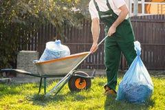 Le jardinier en forme verte nettoie des feuilles dans la cour Pr?s de lui est un chariot avec le compost images stock