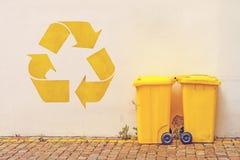 Le jaune deux réutilisent des poubelles sur la rue image stock
