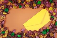 Le jaune enveloppent entouré par le cadre sec coloré de fleurs et de feuilles Vue supérieure, configuration plate Copiez l'espace Photographie stock