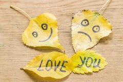 Le jaune part avec une photo d'un visage heureux et triste et de l'AMOUR d'inscription VOUS Photos stock