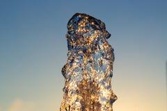 Le jet de loseup de ¡ de Ð de l'eau d'une fontaine frappée contre un ciel bleu, les baisses du miroitement de l'eau au soleil et  images libres de droits