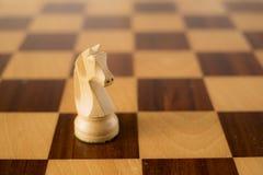Le jeu d'échecs en bois, le cheval blanc/adoubent à bord Image stock
