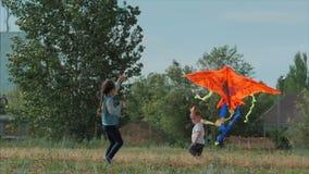 Le jeu d'enfants de vue arrière avec un cerf-volant, une petite fille et un garçon a laissé un serpent volant dans le pré Heureux clips vidéos