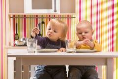 Le jeu de frère et de soeur de bébé de famille mangent le repas dans la cuisine de jouet Image libre de droits
