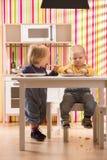 Le jeu de frère et de soeur de bébé de famille mangent le repas dans la cuisine de jouet Images libres de droits