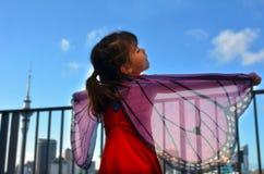 Le jeu de petite fille feignent pour être un papillon images stock