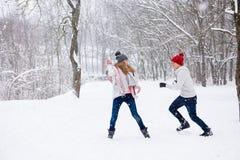Le jeu des jeunes lance des boules de neige dans la forêt d'hiver Photographie stock