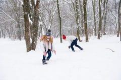 Le jeu des jeunes lance des boules de neige dans la forêt d'hiver Photographie stock libre de droits
