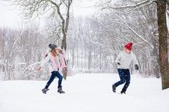 Le jeu des jeunes lance des boules de neige dans la forêt d'hiver Photo libre de droits