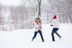 Le jeu des jeunes lance des boules de neige dans la forêt d'hiver Image stock