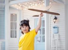 Le jeu heureux de garçon avec l'avion à disposition, enfant rêve du traveli Images libres de droits