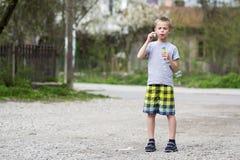 Le jeune écolier blond bel dans les vêtements décontractés avec l'expression sérieuse drôle souffle les ampoules transparentes de photographie stock libre de droits