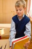 Le jeune écolier emballe des livres derrière un bureau d'école images stock
