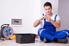 Le jeune électricien travaillant à la prise à la maison Photos stock
