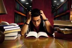 Le jeune étudiant adulte affiche le livre à la bibliothèque image libre de droits