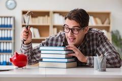 Le jeune étudiant cassant la tirelire pour acheter des manuels Image libre de droits