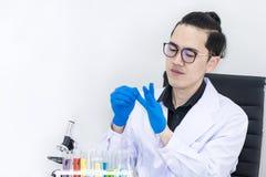 Le jeune étudiant en médecine bel a mis dessus des gants près des microscopes photos stock