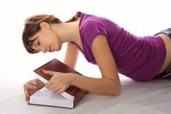 Le jeune étudiant regarde dans le livre Photos libres de droits